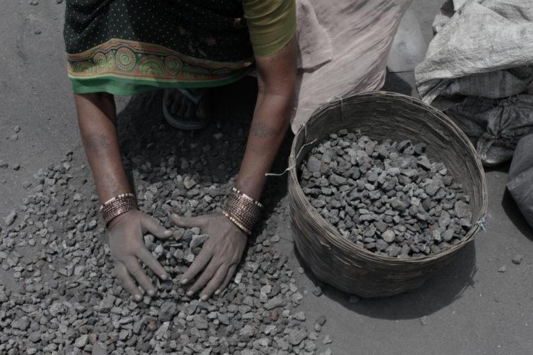झारखंड के खनन क्षेत्र में एक महिला कोयला चुनते हुए
