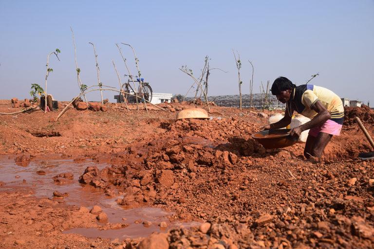 पन्ना के हीरा खदान में रामप्यारे मिट्टी से सने कंकड़ों को धो रहे हैं। इन्हीं कंकड़ों में से हीरा मिलने की संभावना रहती है। तस्वीर- मनीष चंद्र मिश्र/मोंगाबे-हिन्दी