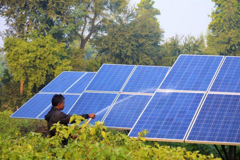 सौर ऊर्जाः सोलर पैनल की सफाई करता एक किसान। तस्वीर- अथर परवेज