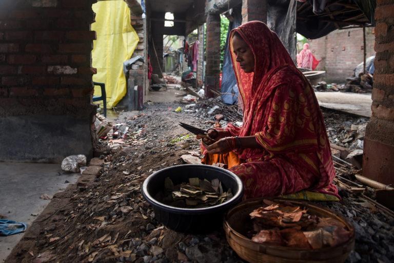 राकिमा बीबी घर उजड़ने के बाद एक अस्थायी स्थान पर बीड़ी बनाने का काम कर रही हैं। इस इलाके में बीड़ी का कारोबार होता है। तस्वीर- तन्मय भादुरी