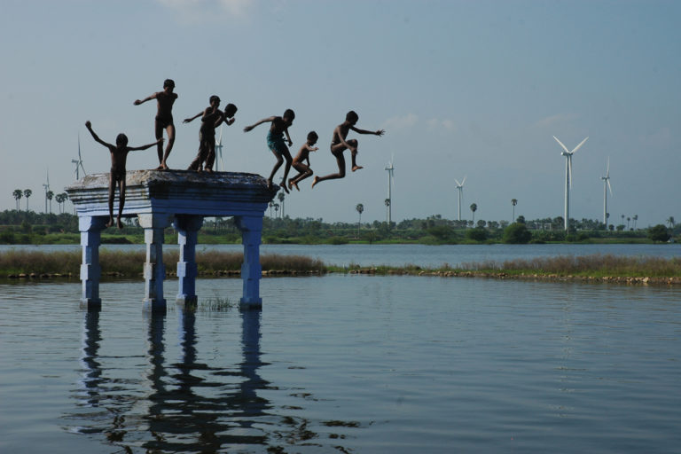 विंड टरबाइन की पृष्ठभूमि में तालाब में खेलते बच्चे। भारत ने वर्ष 2030 तक अक्षय ऊर्जा की अपनी क्षमता 450 मेगावाट करने की ठानी है। प्रतीकात्मक तस्वीर- वेस्तास/याहू/फ्लिकर