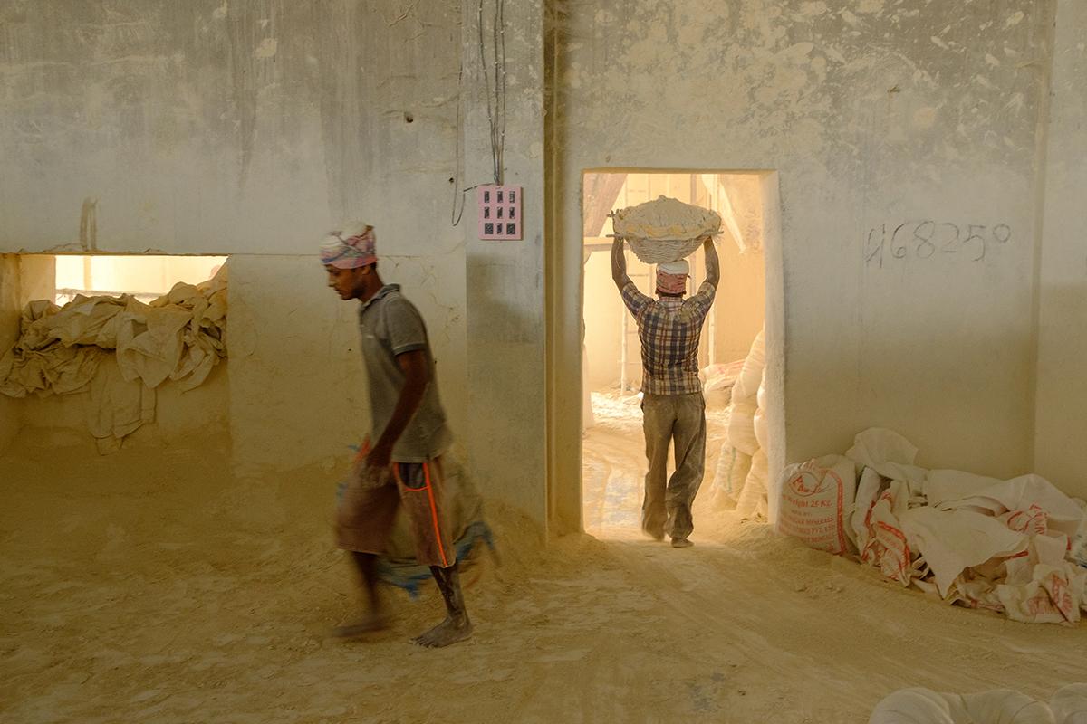 चीनी मिट्टी के प्रसंस्करण इकाई में काम करते मजदूर। तस्वीर- सुभ्रजीत सेन