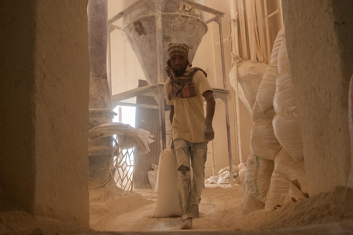 चीनी मिट्टी पीसने वाली मशीन के सामने काम करता एक मजदूर। तस्वीर- सुभ्रजीत सेन