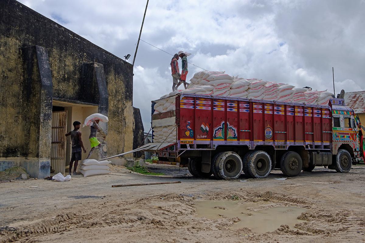 भारी वाहनों से चीनी मिट्टी लोड करते मजदूर। तस्वीर- सुभ्रजीत सेन