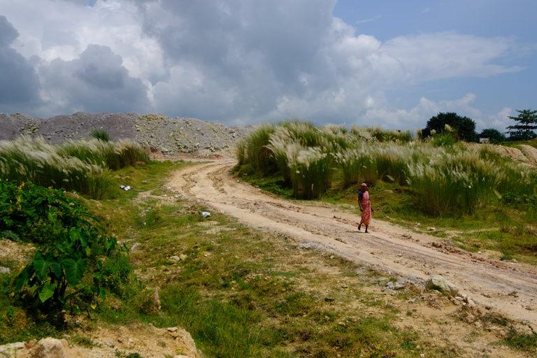 चीनी मिट्टी खदान से निकले मलबे के बीच से गुजरती एक महिला। इन रास्तों से अक्सर बड़ी गाड़ियां खनिज लेकर गुजरती हैं। तस्वीर- सुभ्रजीत सेन