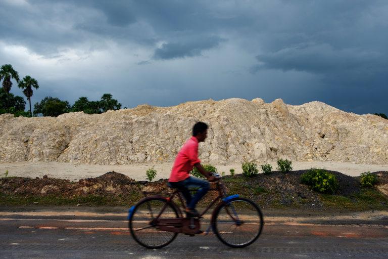 पश्चिम बंगाल के खारिया में सड़क के किनारे फेंके गए चीनी मिट्टी खनन से निकले मलबे के पास से साइकिल से गुजरता एक ग्रामीण। तस्वीर- सुभ्रजीत सेन